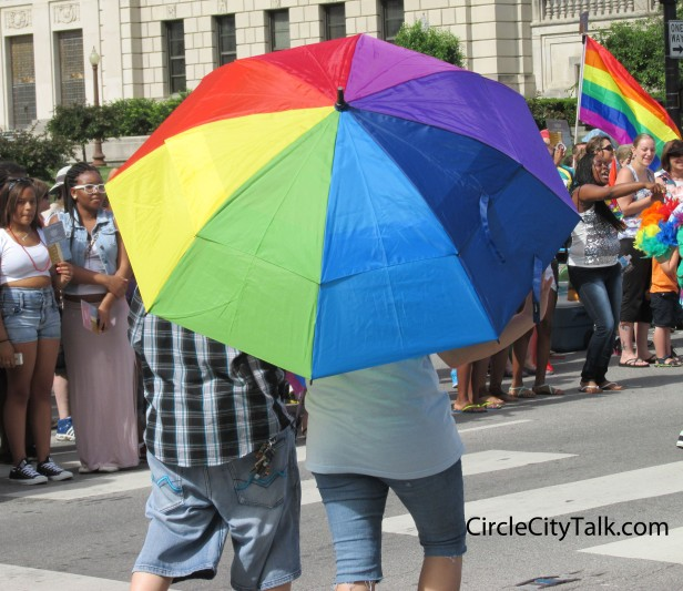 Even tough there wasn't a cloud in the sky, a couple walks the parade route together under a rainbow umbrella.